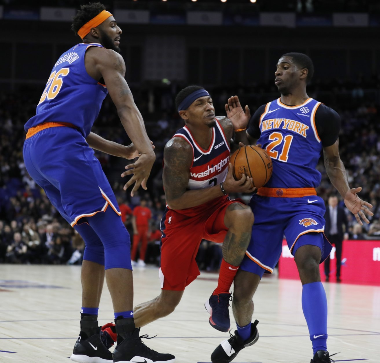 Washington Wizards guard Bradley Beal (3),center, drives to the basket flanked by New York Knicks center Mitchell Robinson (26), left, and his teammate guard Damyean Dotson (21), during an NBA basketball game between New York Knicks and Washington Wizards at the O2 Arena, in London, Thursday, Jan.17, 2019. (AP Photo/Alastair Grant)