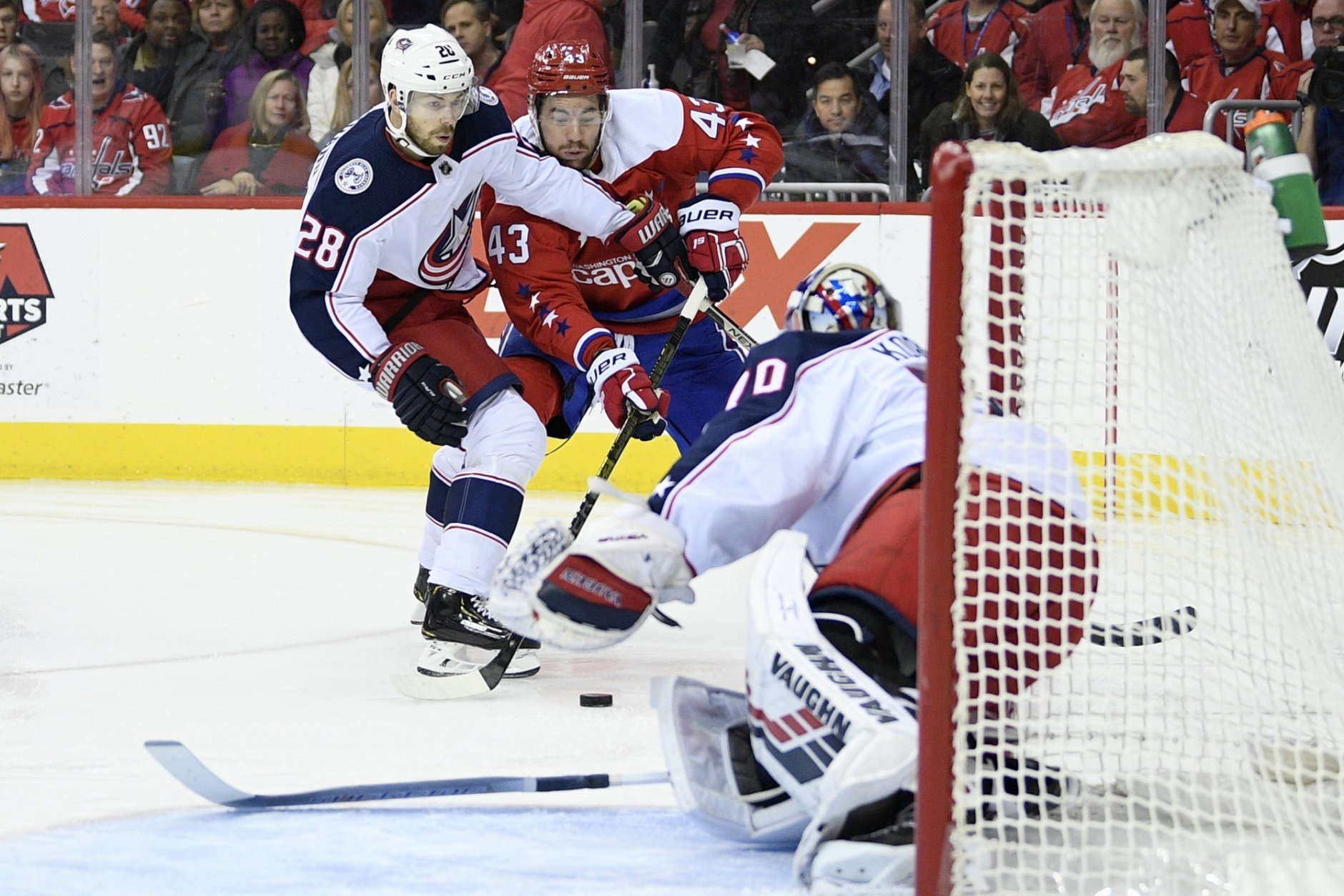 Washington Capitals right wing Tom Wilson (43) battles for the puck against Columbus Blue Jackets right wing Oliver Bjorkstrand (28), of Denmark, and goaltender Joonas Korpisalo (70), of Finland, during the first period of an NHL hockey game, Saturday, Jan. 12, 2019, in Washington. (AP Photo/Nick Wass)