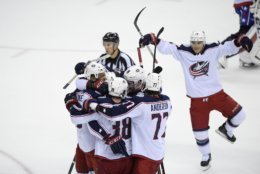 Columbus Blue Jackets right wing Josh Anderson (77), center Boone Jenner (38), and others celebrate after a goal scored by left wing Artemi Panarin (9) during overtime of an NHL hockey game against the Washington Capitals, Saturday, Jan. 12, 2019, in Washington. (AP Photo/Nick Wass)