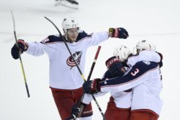 Columbus Blue Jackets left wing Artemi Panarin (9), of Russia, celebrates his goal with defenseman Seth Jones (3) and center Pierre-Luc Dubois (18) during overtime of an NHL hockey game against the Washington Capitals, Saturday, Jan. 12, 2019, in Washington. (AP Photo/Nick Wass)