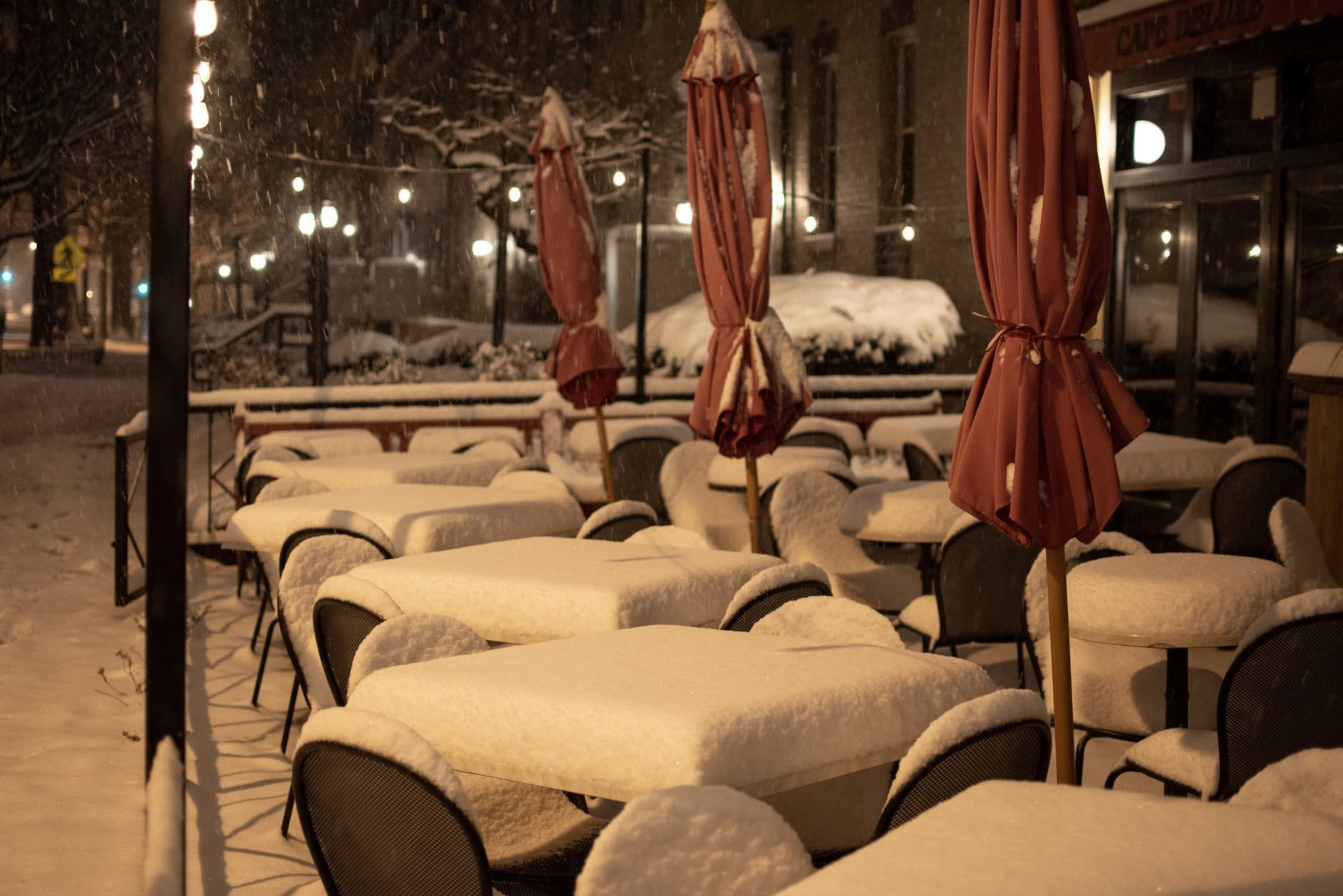Snow accumulating on table outside a restaurant along Wisconsin Avenue in northwest D.C. on Sunday. (WTOP/Alejandro Alvarez)
