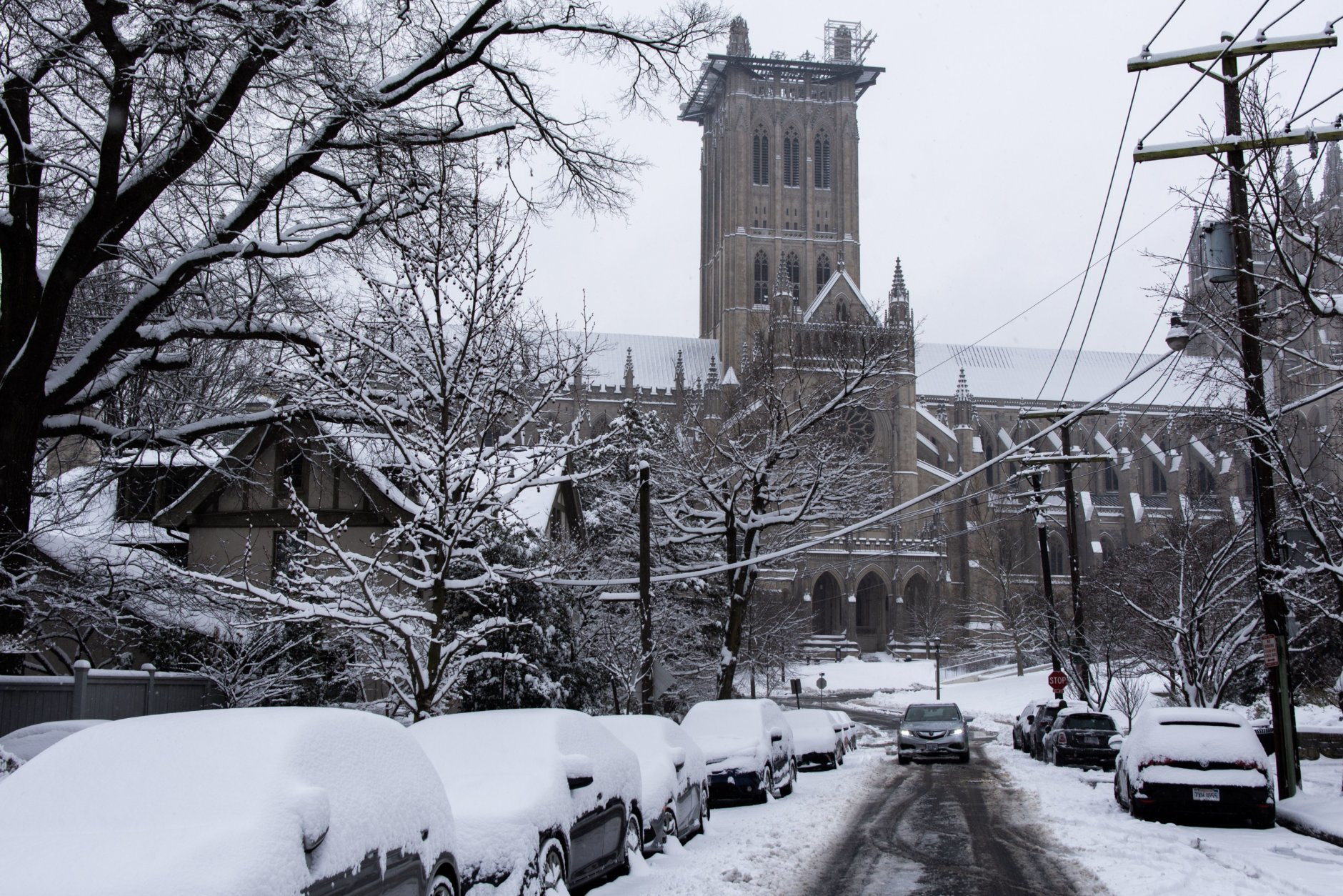 Despite the possibility of more snow, cleanup efforts were already underway and moving at a quick pace in most of D.C. Roadways impassable overnight were largely cleared of snow by mid-morning, though work continued on side streets such as this one near the National Cathedral. (WTOP/Alejandro Alvarez)