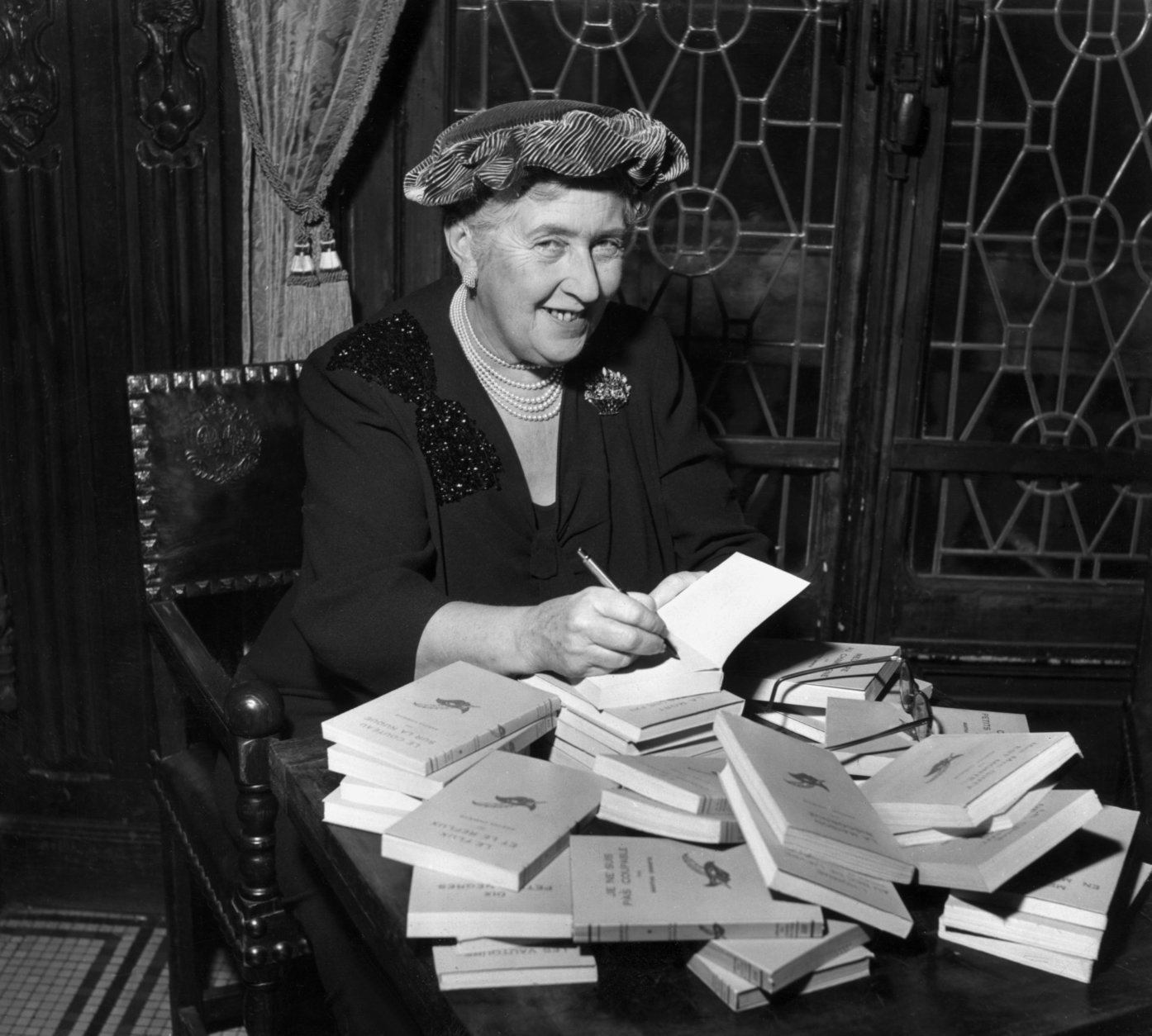 circa 1965:  British mystery author Agatha Christie (1890-1976) autographing French editions of her books.  (Photo by Hulton Archive/Getty Images)