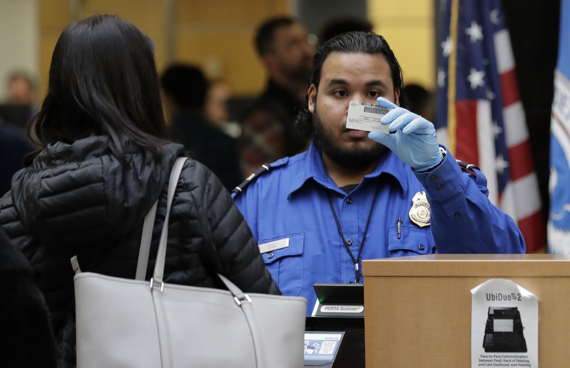 A TSA worker checks an identification card, Friday, Jan. 25, 2019, at Seattle-Tacoma International Airport in Seattle. Yielding to mounting pressure and growing disruption, President Donald Trump and congressional leaders on Friday reached a short-term deal to reopen the government for three weeks while negotiations continue over the president's demands for money to build his long-promised wall at the U.S.-Mexico border. (AP Photo/Ted S. Warren)