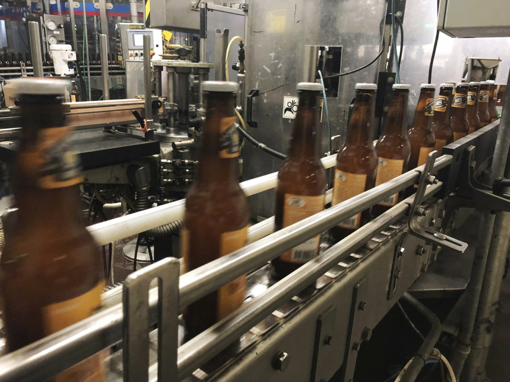 FILE- In this Jan. 14, 2019, file photo, bottles, freshly filled with beer, move on a belt at Lakefront Brewery in Milwaukee. Some craft breweries are postponing new beer releases or expansions because they need permission from a federal agency that isn't open. Such breweries tend to offer new seasonal and special brews frequently, and new beer labels need the Alcohol and Tobacco Tax and Trade Bureau's approval to be sold across state lines.(AP Photo/Carrie Antlfinger, File)
