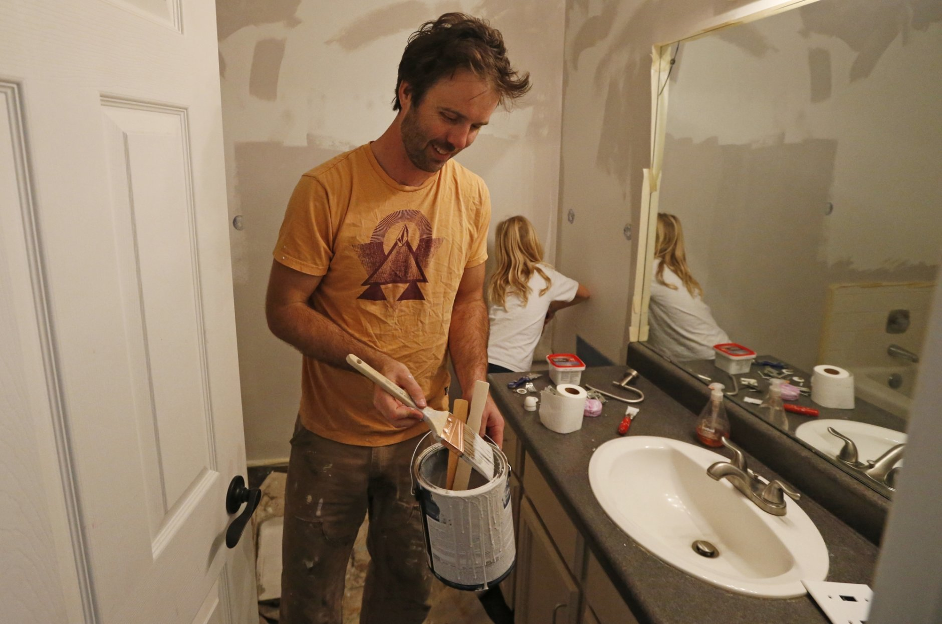 Federal contractor Chris Erickson paints his bathroom Friday, Jan., 4, 2019, in North Salt Lake, Utah. Erickson says he'll run out of vacation days if the shutdown continues. The father of three from Salt Lake City will then crack into his savings, and he'll likely postpone a 14th wedding anniversary trip with his wife to a cabin. Erickson said he likely won't get the chance for reimbursement for the lost days because he's a contractor. (AP Photo/Rick Bowmer)