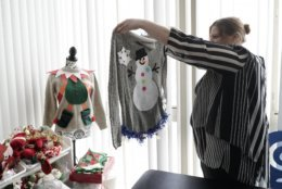 """Doris Cochran holds """"an ugly sweater,"""" which she is planning to sell, Friday, Jan. 18, 2019 in her apartment in Arlington, Va., Cochran is a disabled mother of two young boys living in subsidized housing in Arlington, Virginia. She's stockpiling canned foods to try to make sure her family won't go hungry if her food stamps run out. She says she just doesn't know """"what's going to happen"""" and that's what scares her the most.  (AP Photo/Sait Serkan Gurbuz)"""