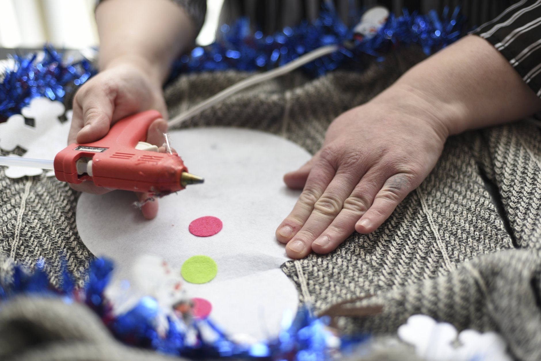 """Doris Cochran works on """"an ugly sweater,"""" which she is planning to sell, Friday, Jan. 18, 2019 in her apartment in Arlington, Va., Cochran is a disabled mother of two young boys living in subsidized housing in Arlington, Virginia. She's stockpiling canned foods to try to make sure her family won't go hungry if her food stamps run out. She says she just doesn't know """"what's going to happen"""" and that's what scares her the most.  (AP Photo/Sait Serkan Gurbuz)"""