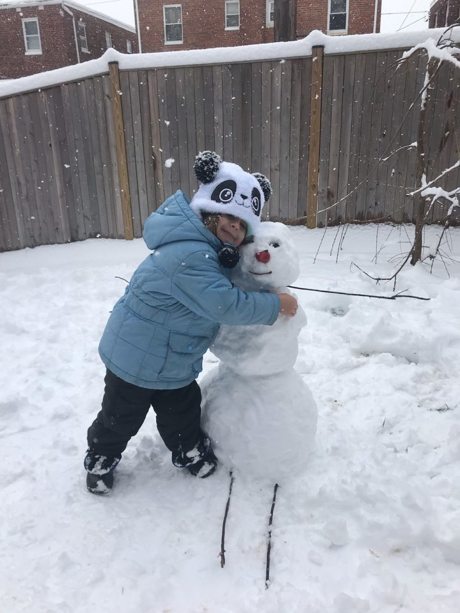 Molly Valm gives her new snowy friend a warm hug. (Courtesy of Steven Valm)