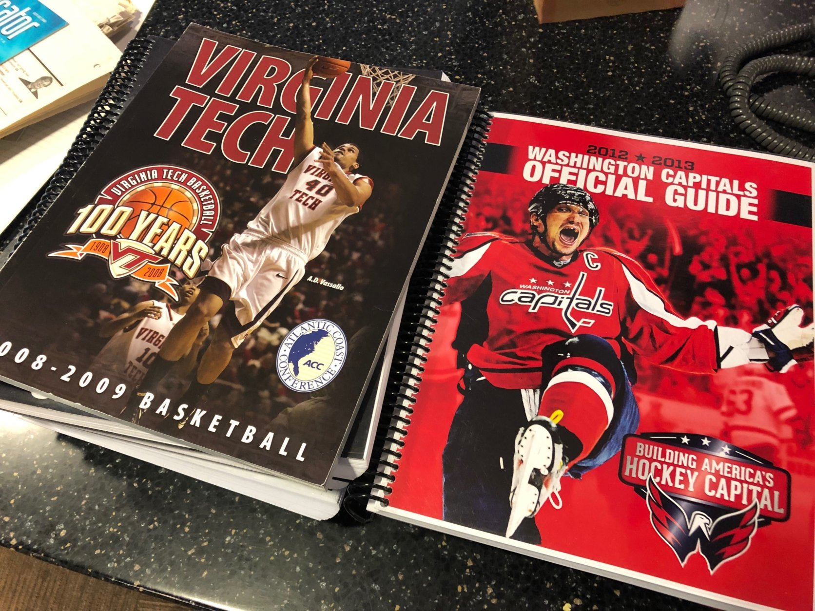 Sports media guides are taking up a sizable chunk of real estate on The Football Table. Who's up for a 2008-2009 Virginia Tech Hokies guide? Get some insight into how they finished 19-15, (WTOP/Julia Ziegler)