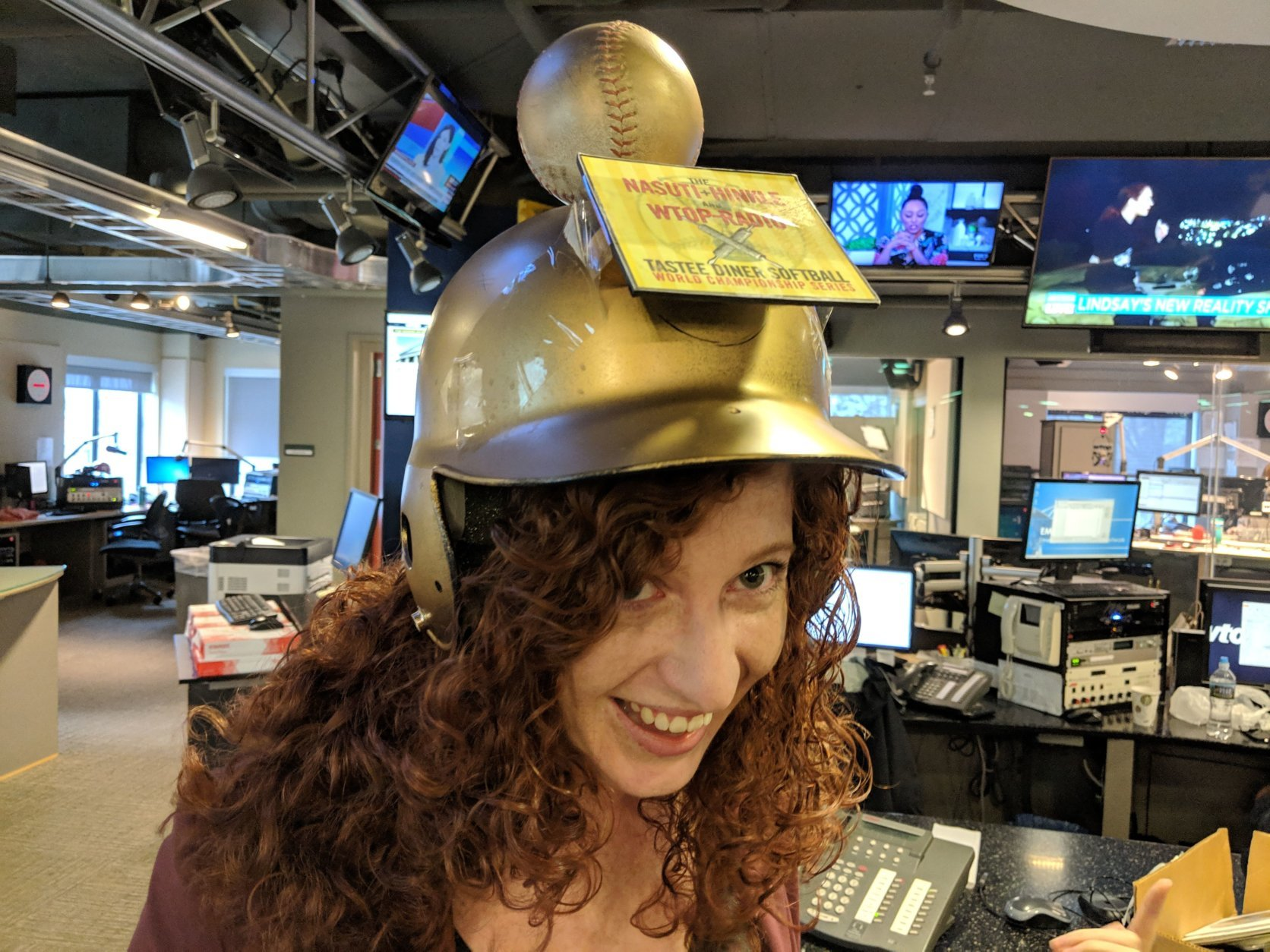 "Afternoon news writer Keara Dowd models ""The Nasuti + Hinkle and WTOP-Radio Tastee Diner Softball World Championship Series"" trophy. (WTOP/Jack Pointer)"