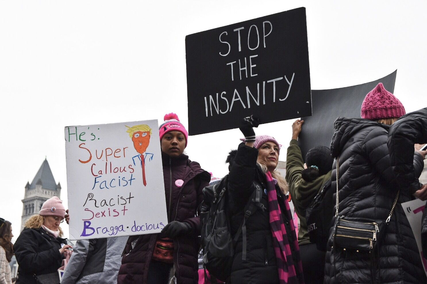 The protesters at the Women's March main stage at Freedom Plaza on the morning of Jan. 19, with the Trump International Hotel in the backdrop. (WTOP/Alejandro Alvarez)