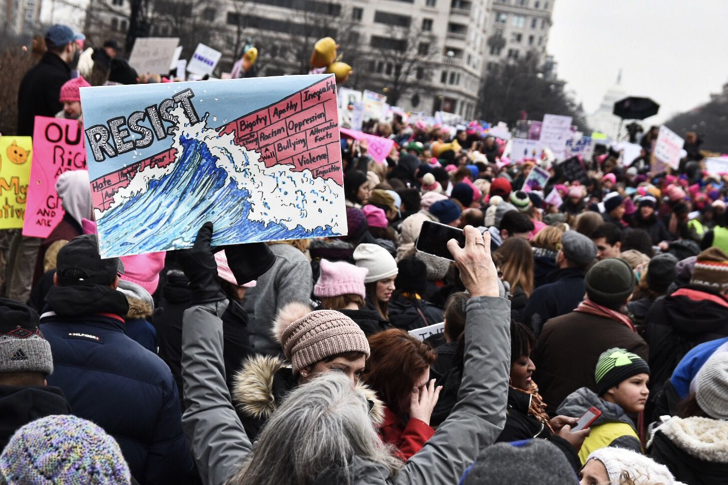A Women's March protester holds a sign with a blue wave, a common trope signifying Democratic victory in the run-up to the 2018 election. (WTOP/Alejandro Alvarez)