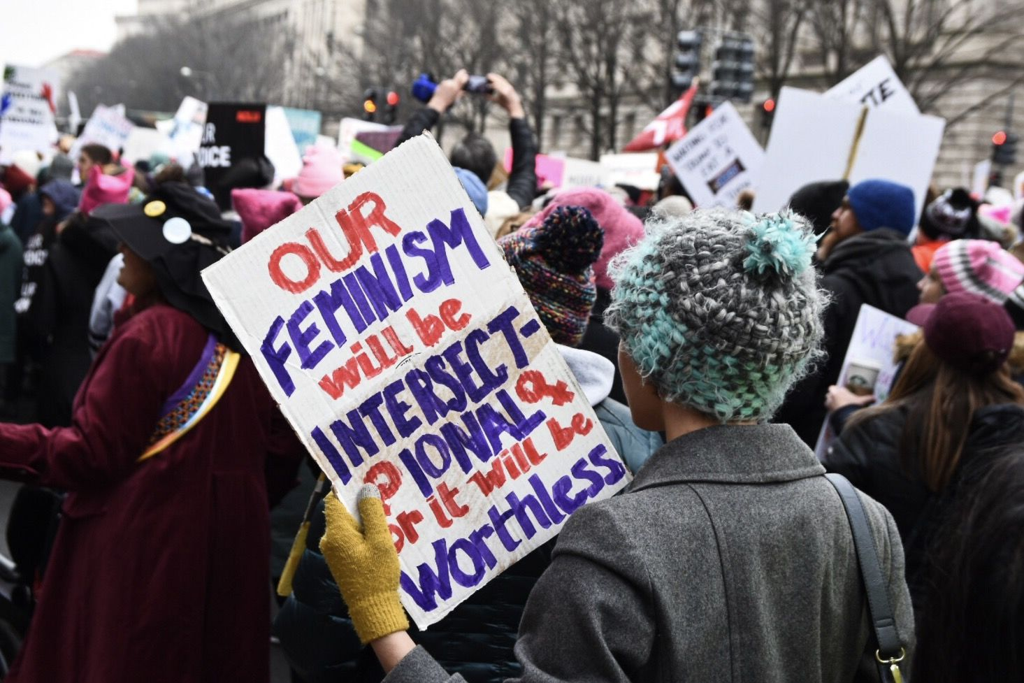 A protester rounds the corner of Pennsylvania Avenue onto 11th Street. The Women's March has recently faced criticism over a lack of inclusiveness among its organizing. (WTOP/Alejandro Alvarez)