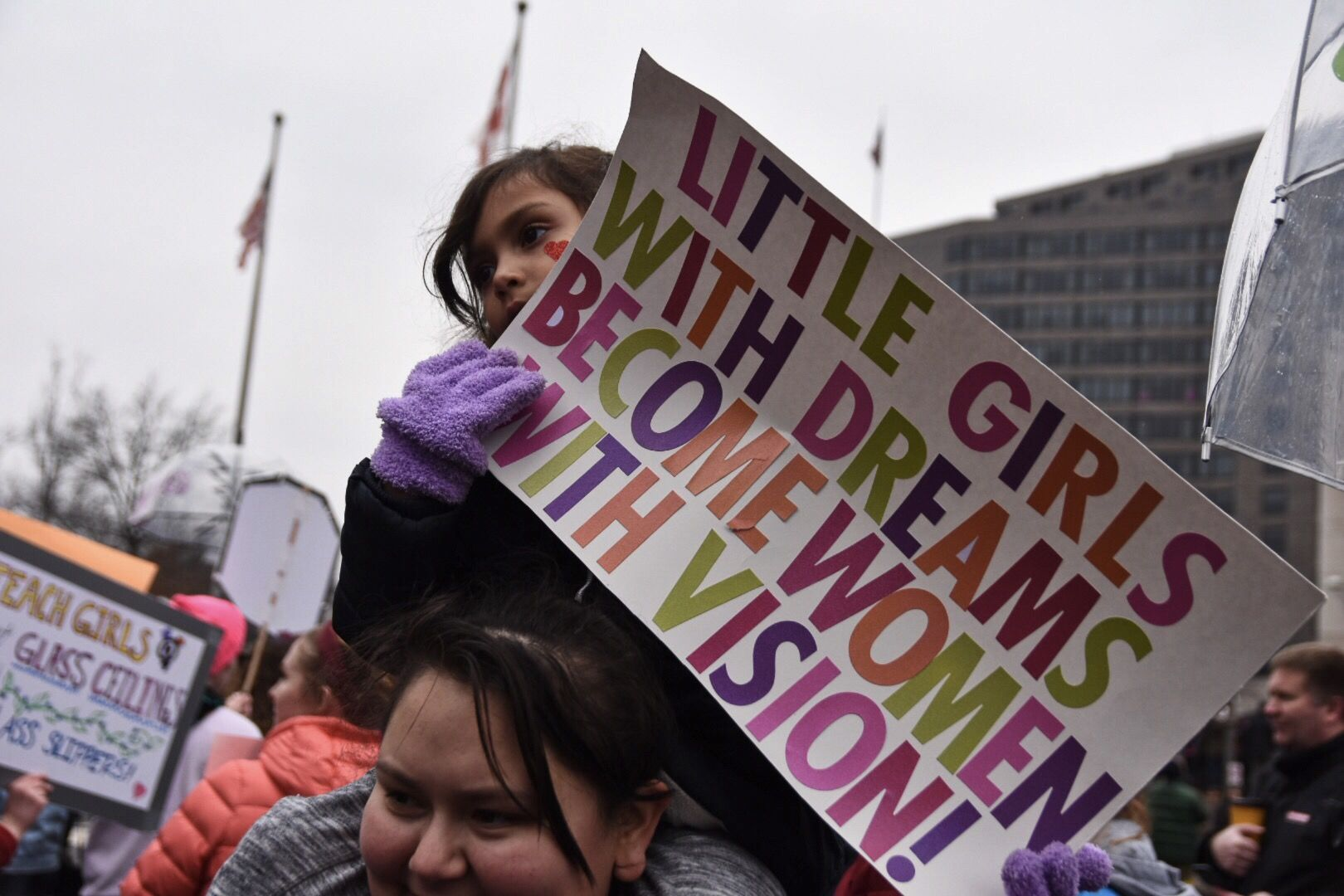 A young girl sits on her mother's shoulders at Freedom Plaza following the march. (WTOP/Alejandro Alvarez)