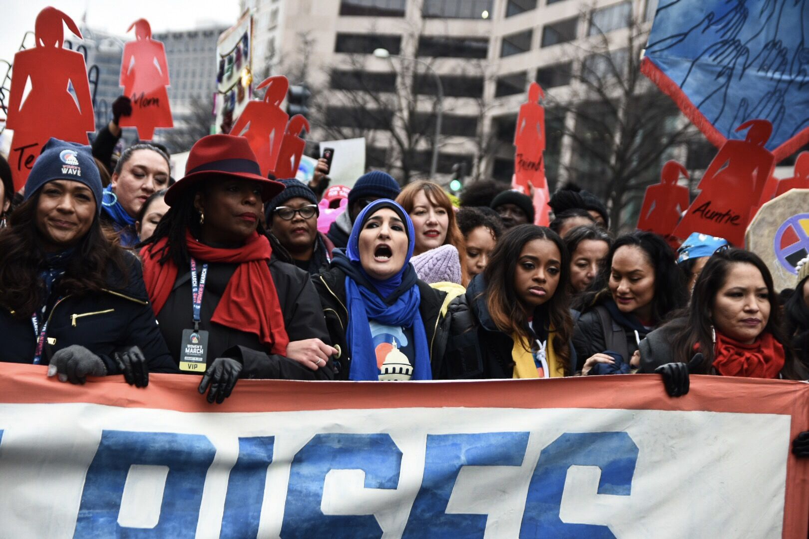 Women's March organizers Linda Sarsour (center), Tamika Mallory and Bob Bland lead a chant behind a banner at the front of the Women's March procession before the start of the march near the Trump International Hotel. (WTOP/Alejandro Alvarez)