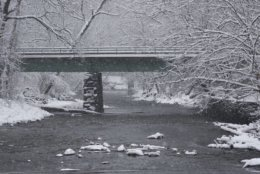 Snow falls on a bridge in Rock Creek Park. (WTOP/Dave Dildine)