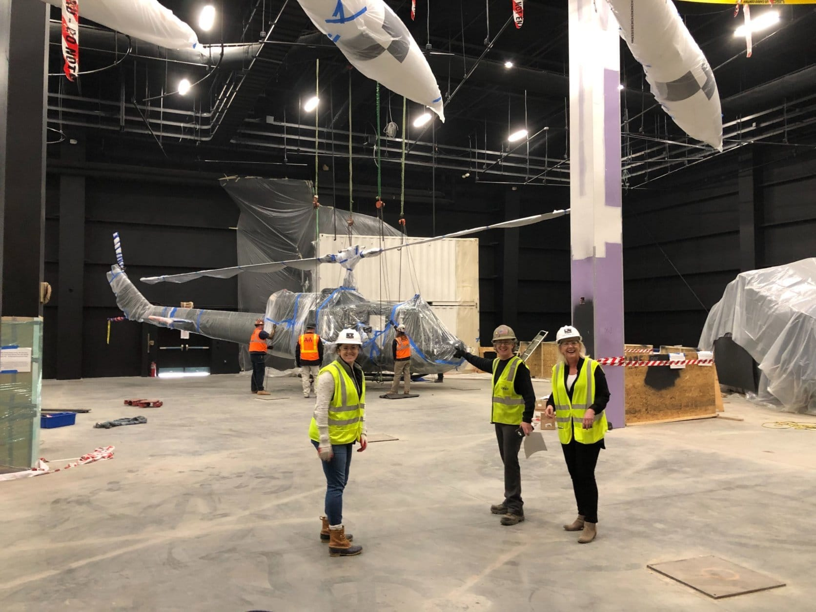 "Three women lead the lift mission to install the UH-1B Iroquois ""Huey"" helicopter in the museum's historic gallery section. (WTOP/Kristi King)"