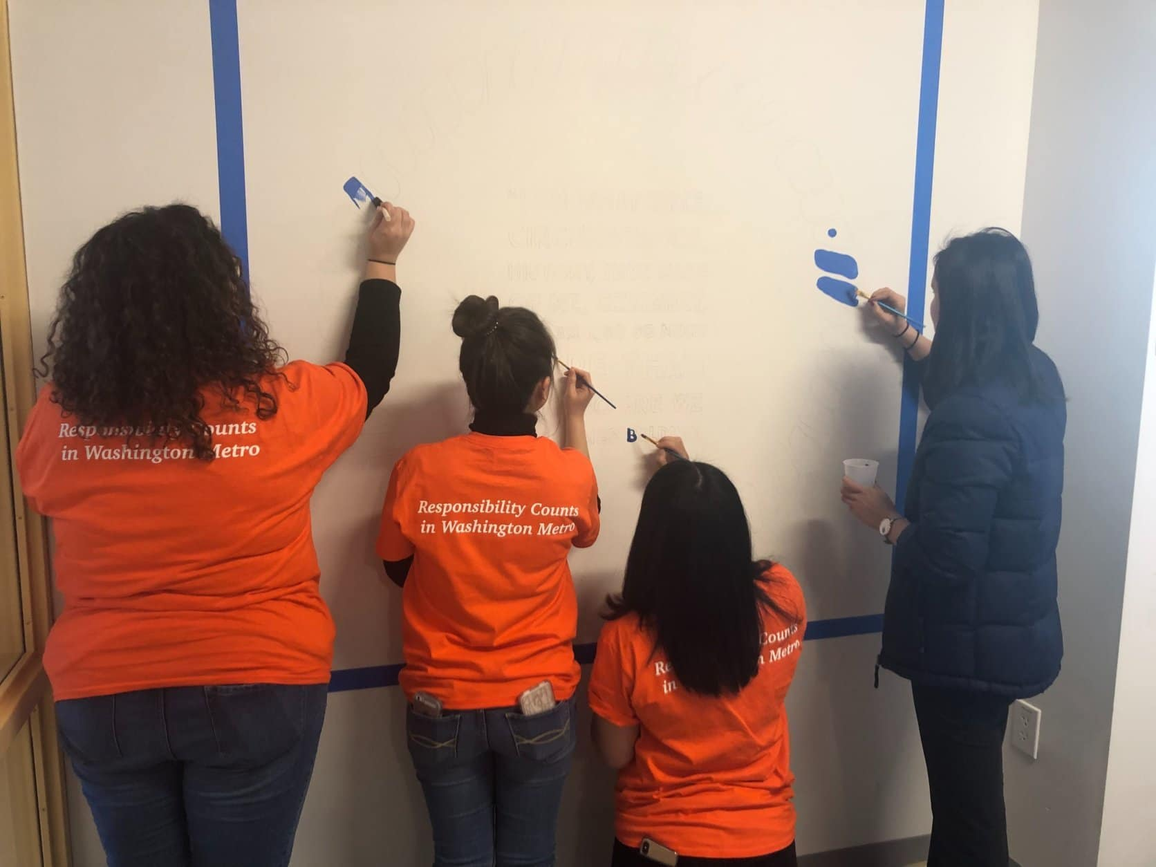 Volunteers paint a wall as part of the City Year MLK Day of Service at Ron Brown College Preparatory High School. (WTOP/Melissa Howell)