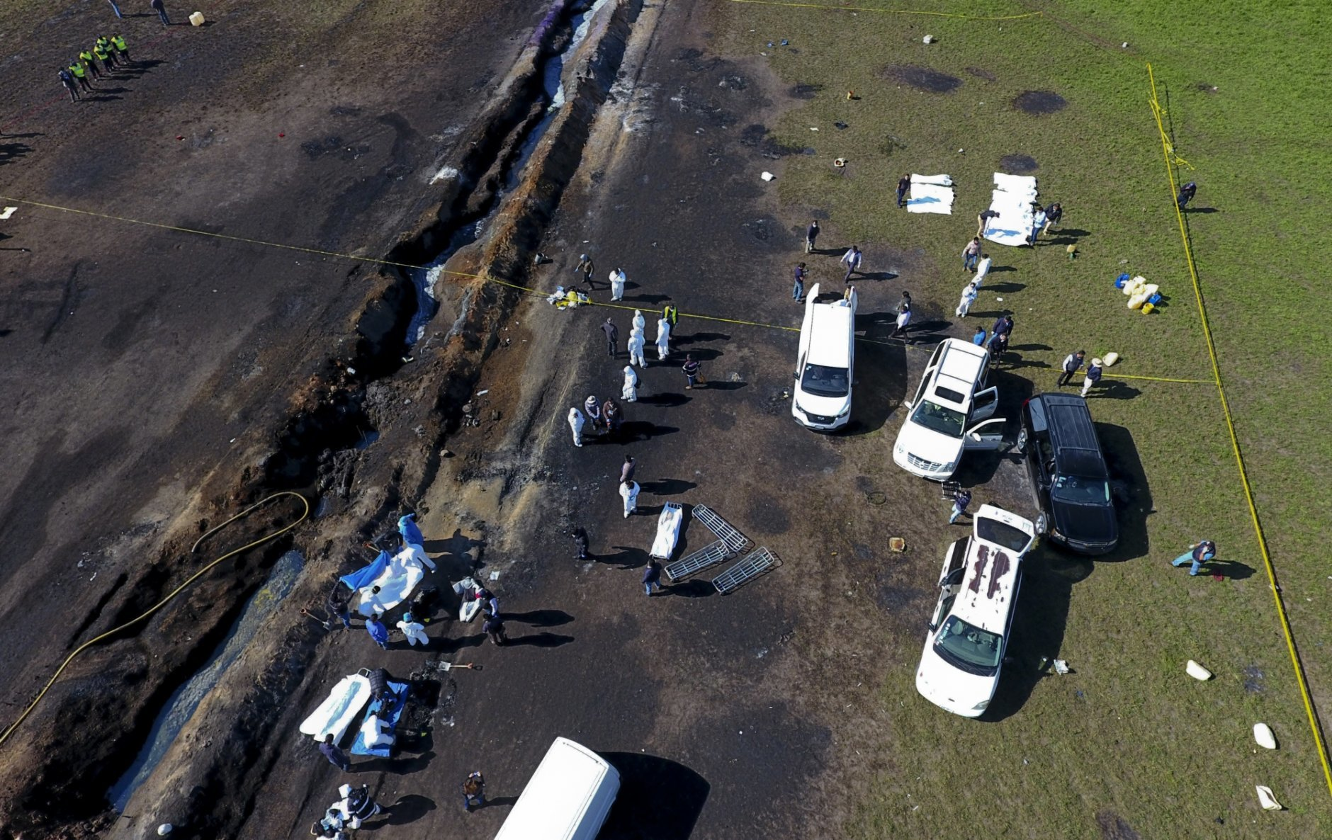 Forensic experts work the area an oil pipeline explosion in Tlahuelilpan, Hidalgo state, Mexico, Saturday, Jan. 19, 2019. A massive fireball that engulfed people scooping up fuel spilling from a pipeline ruptured by thieves in central Mexico killed dozens of people and badly burned many more.  (AP Photo/Claudio Cruz)