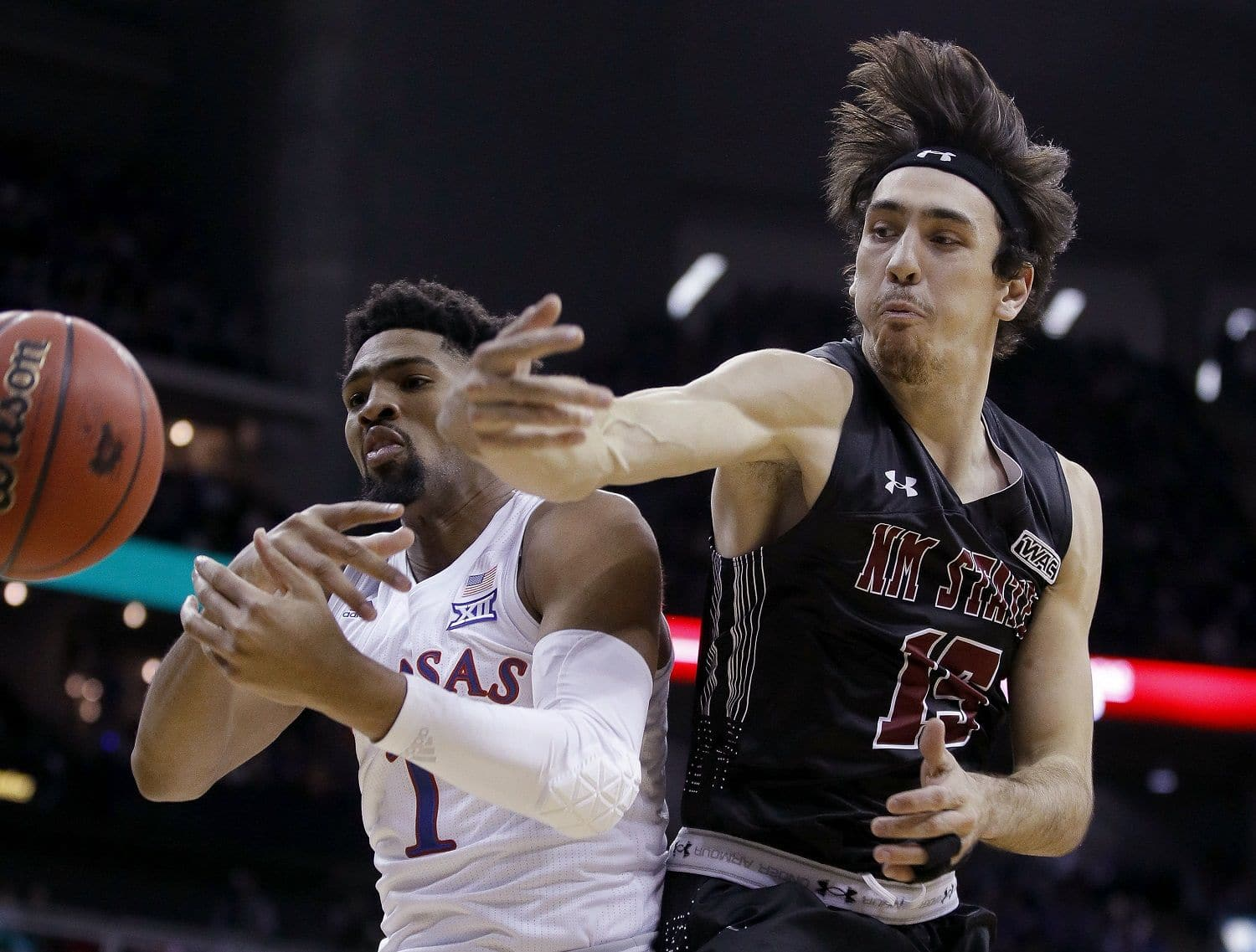 New Mexico State's Ivan Aurrecoechea, right, knocks the ball away from Kansas' Dedric Lawson (1) during the first half of an NCAA college basketball game Saturday, Dec. 8, 2018, in Kansas City, Mo. (AP Photo/Charlie Riedel)