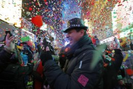 Joey Flores, of California, uses his cellphone as confetti falls during a New Year's celebration in New York's Times Square, Tuesday, Jan. 1, 2019. (AP Photo/Adam Hunger)