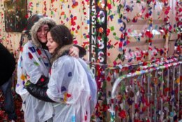 As rain-soaked confetti sticks to most surfaces, revelers embrace in Times Square, early Tuesday, Jan. 1, 2019, as they take part in a New Year's celebration in New York. (AP Photo/Craig Ruttle)
