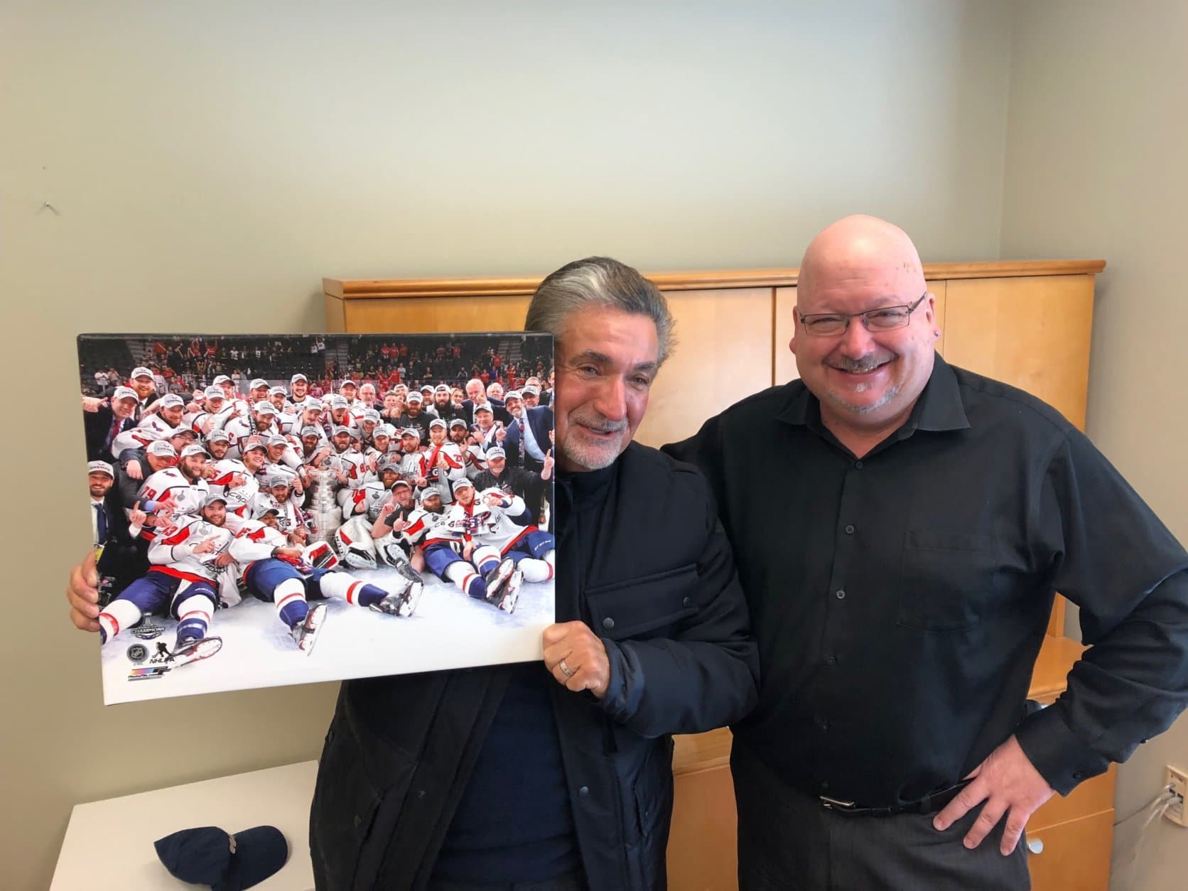 Leonsis never made it into the iconic championship photo, saying he was standing just outside the frame. So he posed with the photo, a copy of which rests in WTOP News & Program Director Mike McMearty's office. (WTOP/Julia Ziegler)
