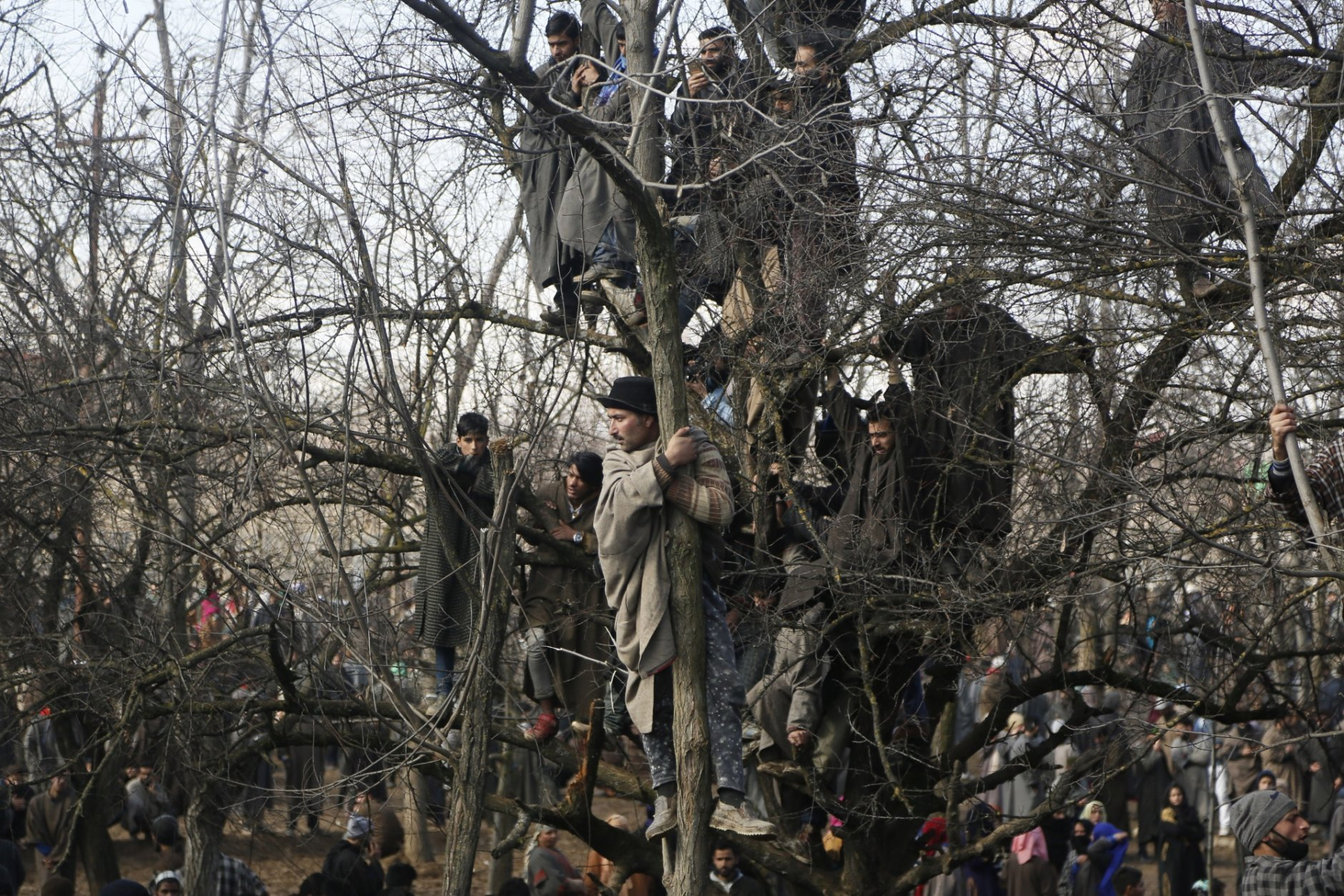 Kashmiri villagers watch the funeral of rebel commander Zeenatul Islam in Sugan village, 61 kilometers (38 miles) south of Srinagar, Indian controlled Kashmir, on Sunday, Jan. 13, 2019. Massive anti-India protests and clashes erupted in disputed Kashmir on Sunday, leading to injuries to at least 16 people after a gunbattle between militants and government forces overnight killed two rebels, police and residents said. (AP Photo/Mukhtar Khan)