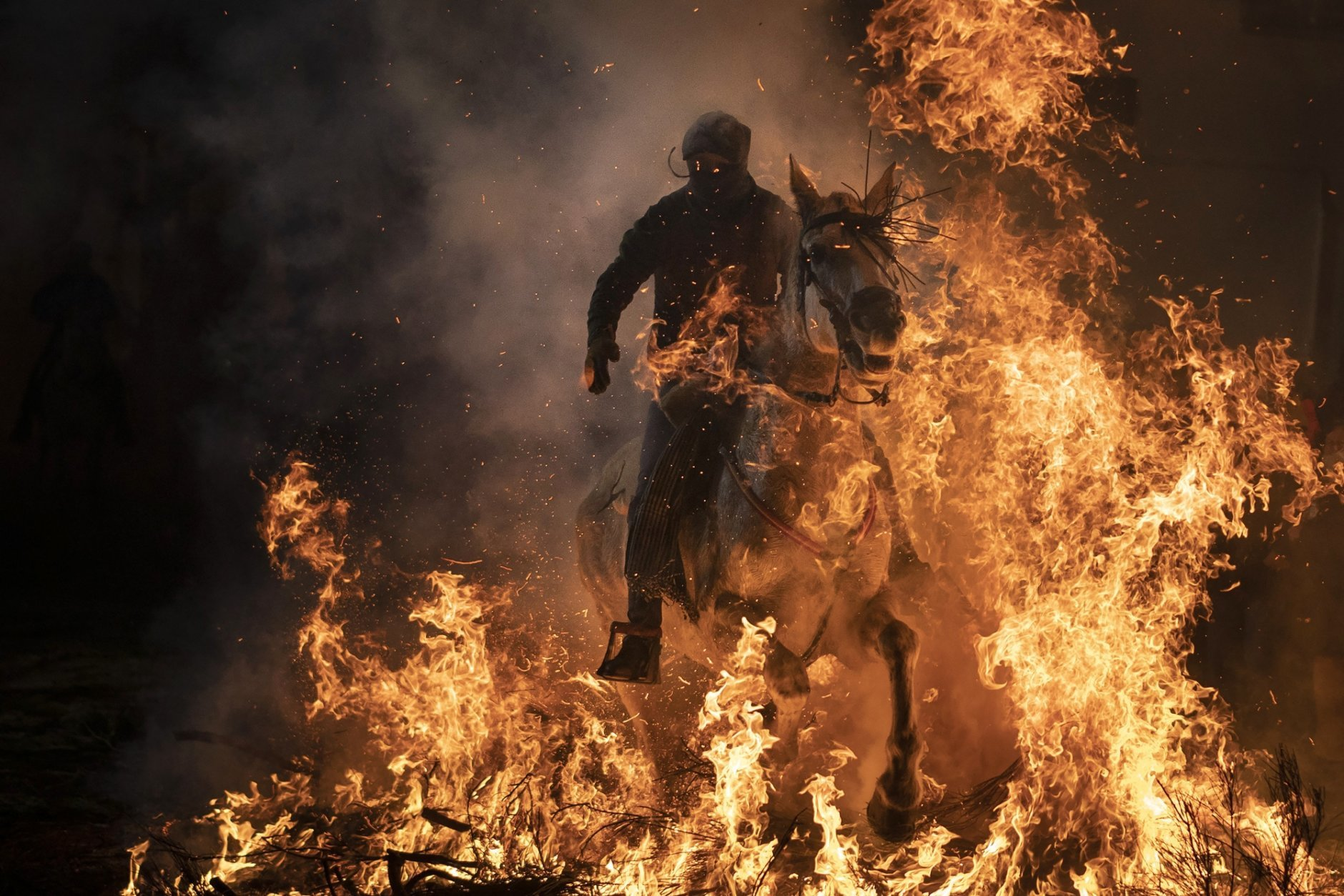 "A man rides a horse through a bonfire as part of a ritual in honor of Saint Anthony the Abbot, the patron saint of domestic animals, in San Bartolome de Pinares, Spain, Wednesday, Jan. 16, 2019. On the eve of Saint Anthony's Day, dozens ride their horses through the narrow cobblestone streets of the small village of San Bartolome during the ""Luminarias,"" a tradition that dates back 500 years and is meant to purify the animals with the smoke of the bonfires and protect them for the year to come. (AP Photo/Felipe Dana)"