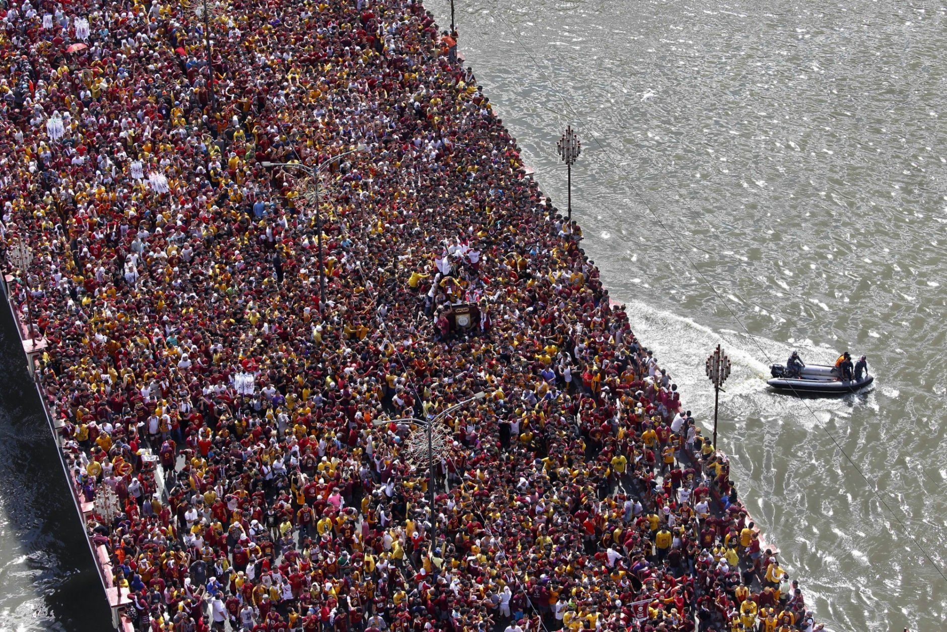 Philippine Coast Guard members keep watch as Roman Catholic devotees cross a bridge in a procession of the Black Nazarene to celebrate its feast day Wednesday, Jan. 9, 2019, in Manila, Philippines. Tens of thousands joined the annual procession of a centuries-old statue of Jesus Christ to celebrate the Feast of the Black Nazarene which usually ends before dawn the next day. (AP Photo/Bullit Marquez)