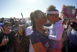 Rashaunda Jarmon holds her 3-year-old granddaughter, Parker Wallace during a community rally outside a Walmart on East Sam Houston Pkwy N in Houston on Saturday, Jan. 5, 2019 for 7-year-old Jazmine Barnes, who was killed on Sunday. Jazmine was shot to death nearby while riding in a car with her mother and three sisters. (Melissa Phillip/Houston Chronicle via AP)