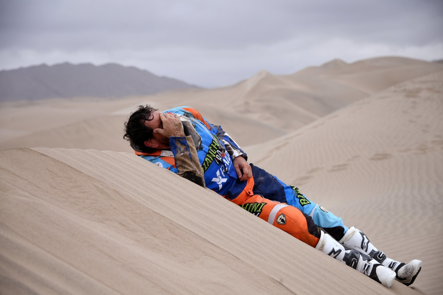 Marcos Colvero of Brazil lies on the dunes after he crashed on his KTM motorbike during the third stage of the Dakar Rally between San Juan de Marcona and Arequipa, Peru, Wednesday, Jan. 9, 2019. (Franck Fife/Pool Photo via AP)