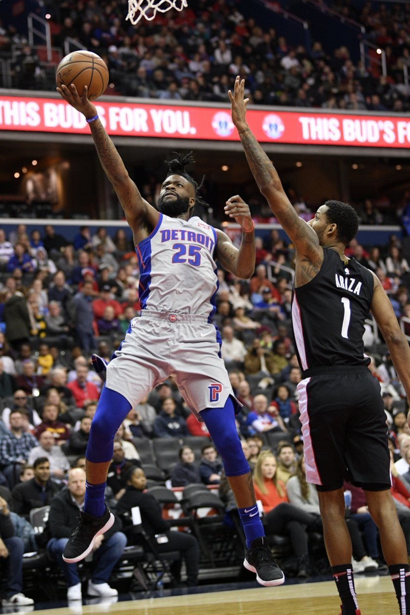 Detroit Pistons guard Reggie Bullock (25) goes to the basket past Washington Wizards forward Trevor Ariza (1) during the first half of an NBA basketball game, Monday, Jan. 21, 2019, in Washington. (AP Photo/Nick Wass)