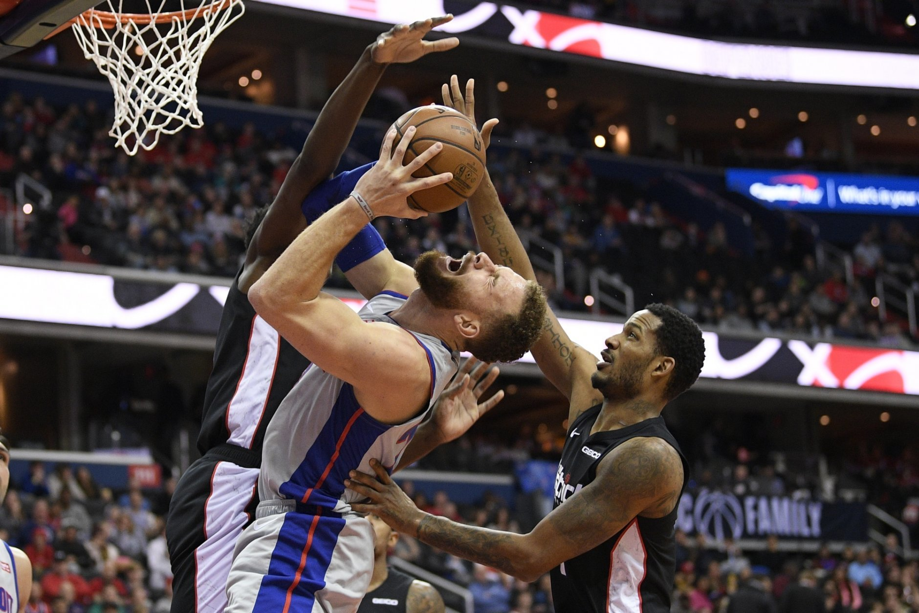 Detroit Pistons forward Blake Griffin, front, is fouled while going against Washington Wizards center Thomas Bryant, back, and forward Trevor Ariza, right, during the first half of an NBA basketball game, Monday, Jan. 21, 2019, in Washington. (AP Photo/Nick Wass)