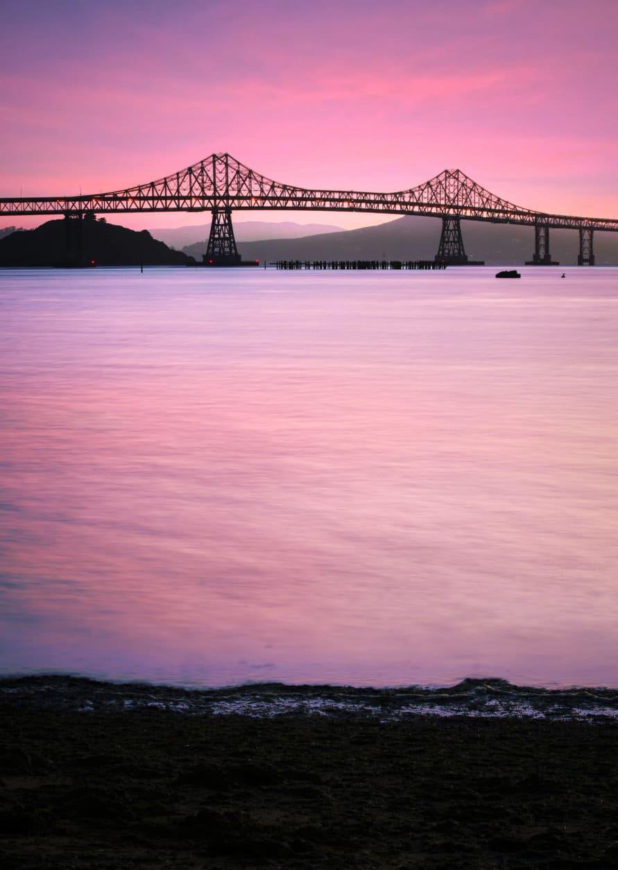 Magenta dusk shot of the Richmond-San Rafael bridge, as seen from Pt. Molate Beach in Richmond, CA, USA.