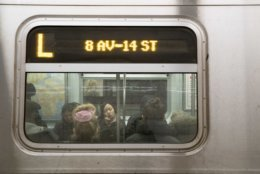 Commuters ride the L train, Thursday, Jan. 3, 2019, in New York. New York Gov. Andrew Cuomo said Thursday, he's calling off a planned 15-month shutdown of the L train, a critical subway link between Manhattan and Brooklyn, saying a team of experts had come up with a way to overhaul a flood-damaged tunnel beneath the East River without closing it or even significantly curtailing service. (AP Photo/Mary Altaffer)