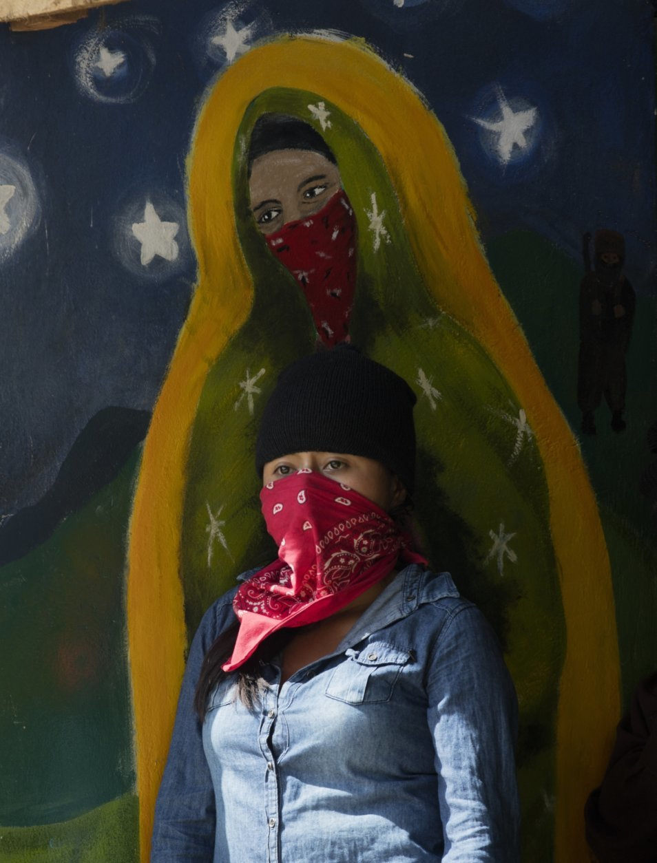 In this Tuesday, Jan. 1, 2019 photo, a masked, female member of the Zapatista National Liberation Army, EZLN, stands by a mural depicting a masked version of the Virgin of Guadalupe, during an event marking the 25th anniversary of the Zapatista uprising in La Realidad, Chiapas, Mexico. Mexico's leftist Zapatistas have continued their aggressive criticism of the country's new president, accusing Andres Manuel Lopez Obrador of dishonesty and vowing to confront him. (AP Photo/Eduardo Verdugo)