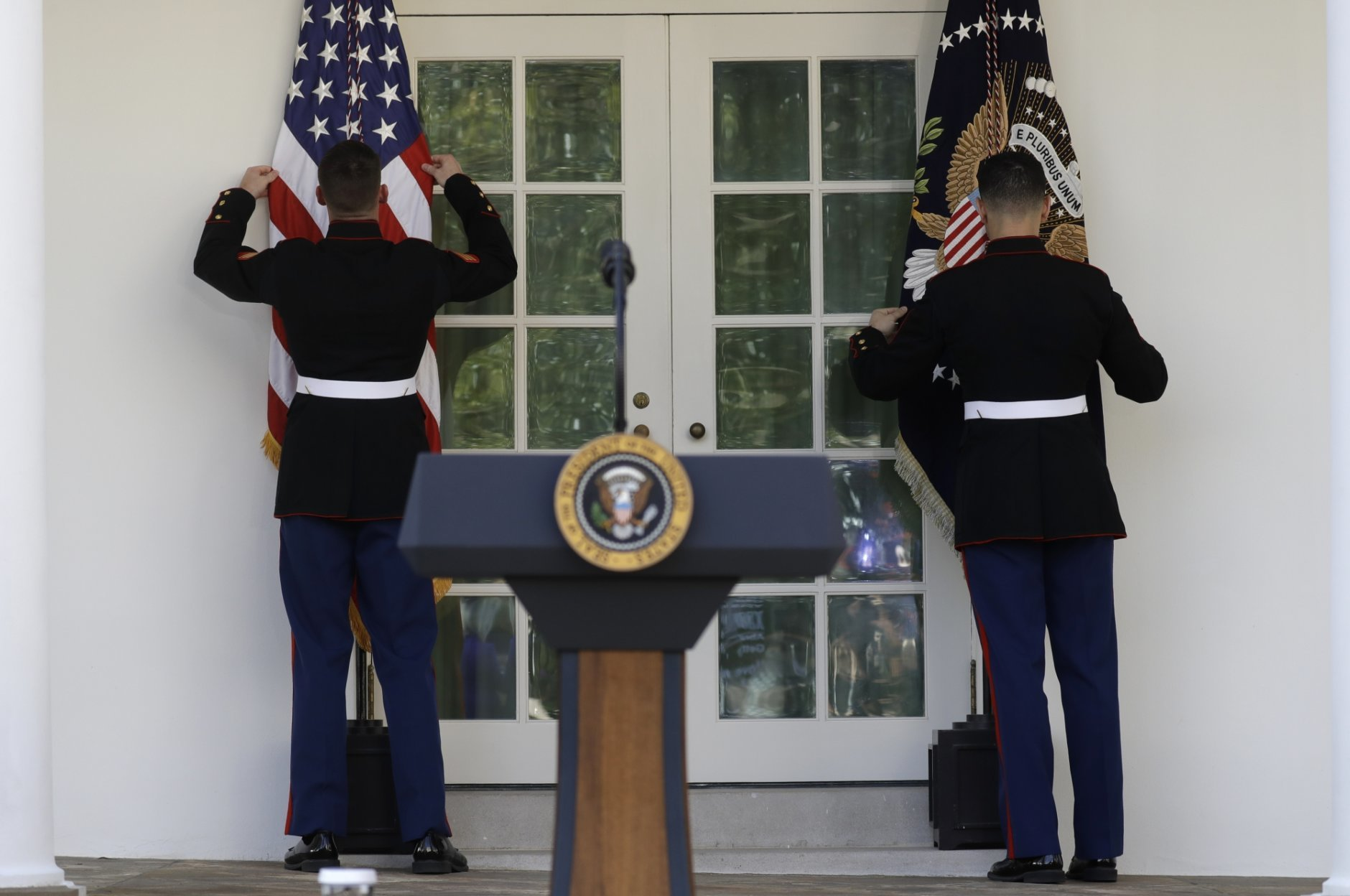 Military aides adjust flags before President Donald Trump speaks in the Rose Garden of the White House, Friday, Jan 25, 2019, in Washington. (AP Photo/ Evan Vucci)