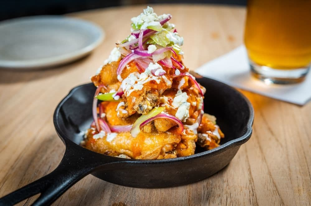 Chicken wings piled high on a cast iron at Mendelsohn's Vim & Victor. (Courtesy Vim & Victor)