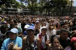 Supporters of opposition leader Juan Guaido listen to him speak at a public plaza in Caracas, Venezuela, Friday, Jan. 25, 2019. The 35-year-old lawmaker's whereabouts had been a mystery since he was symbolically sworn in Wednesday before tens of thousands of cheering supporters, promising to uphold the constitution and rid Venezuela of Maduro's dictatorship. (AP Photo/Fernando Llano)