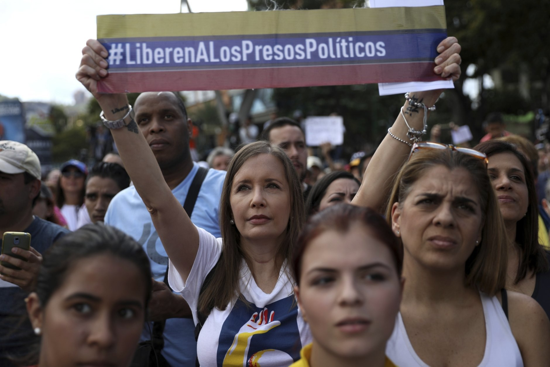 """A member of the opposition holds a banner with a message that reads in Spanish: """"free the political prisoners,"""" during a gathering to propose amnesty laws for police and military, in Las Mercedes neighborhood of Caracas, Venezuela, Saturday, Jan. 29, 2019. Venezuela's political showdown moves to the United Nations where a Security Council meeting called by the United States will pit backers of President Nicolas Maduro against the Trump administration and supporters of the country's self-declared interim leader Juan Guaido. (AP Photo/Rodrigo Abd)"""