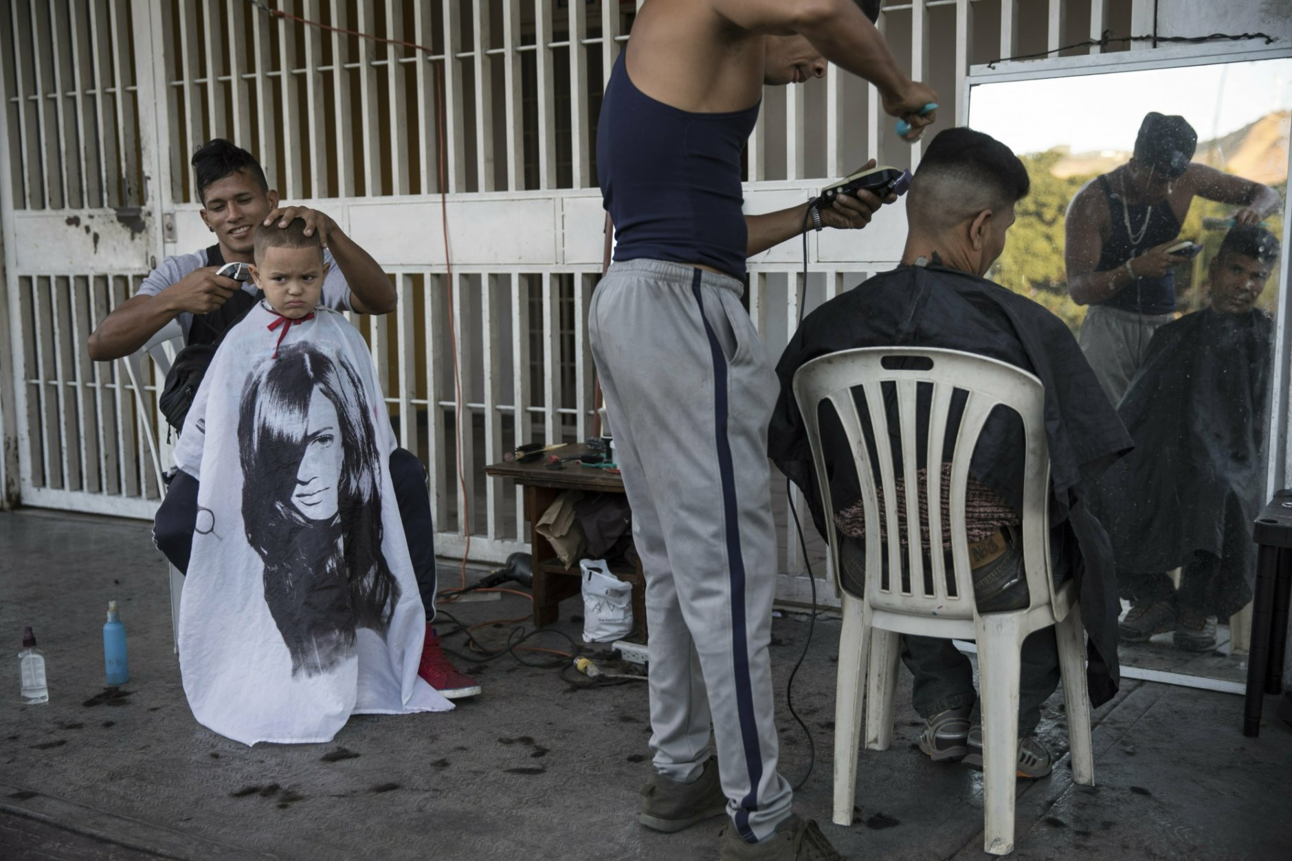 Juan Manuel Marquez, 32, left, cuts the hair of Jean Pierre, 4, at a makeshift barber shop on a sidewalk in Caracas, Venezuela, Friday, Jan. 25, 2019. Juan Manuel charges 1000 bolivars or around .50 cents US for each service. Juan Guaido, the Venezuelan opposition leader who has declared himself interim president appeared in public Friday for the first time in days and vowed to remain on the streets to usher in a transitional government, while President Nicolas Maduro dug in and accused his opponents of orchestrating a coup. (AP Photo/Rodrigo Abd)