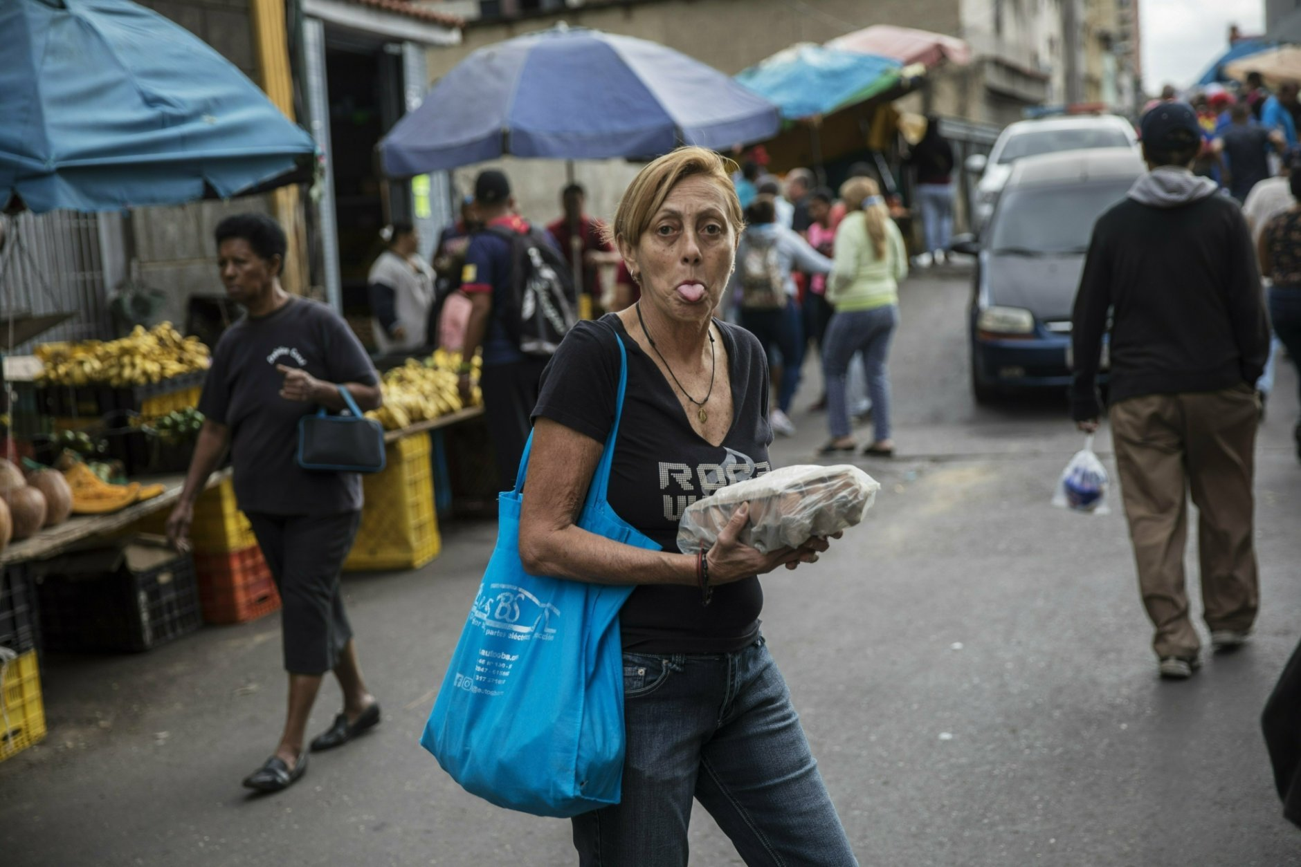 A woman sticks out her tongue as she shops at the Quinta Crespo street market in downtown Caracas, Venezuela, Saturday, Jan. 26, 2019. The country's political showdown moves to the United Nations Saturday where a Security Council meeting called by the United States will pit backers of President Nicolas Maduro against the Trump administration and supporters of the country's self-declared interim leader Juan Guaido. (AP Photo/Rodrigo Abd)