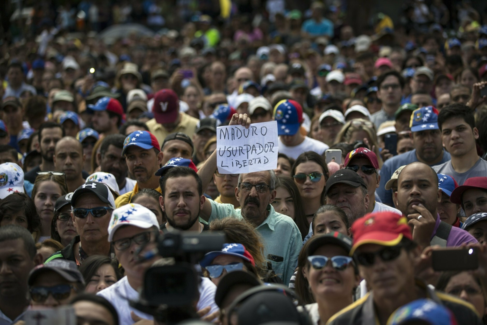 """A man holds a sign with a message that reads in Spanish: """"Maduro, Usurper. Freedom"""" during an opposition rally in Las Mercedes neighborhood of Caracas, Venezuela, Saturday, Jan. 29, 2019. Venezuela's political showdown moves to the United Nations where a Security Council meeting called by the United States will pit backers of President Nicolas Maduro against the Trump administration and supporters of the country's self-declared interim leader Juan Guaido. (AP Photo/Rodrigo Abd)"""