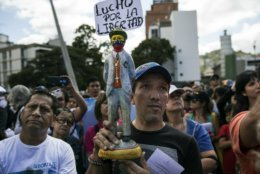 """A man holds a statuette of Venezuelan popular saint Jose Gregorio Hernandez with a sign that reads """"I fight for liberty,"""" as members of the opposition gather to propose amnesty laws for the police and the military, in Las Mercedes neighborhood of Caracas, Venezuela, Saturday, Jan. 29, 2019. Venezuela's political showdown moves to the United Nations where a Security Council meeting called by the United States will pit backers of President Nicolas Maduro against the Trump administration and supporters of the country's self-declared interim leader Juan Guaido. (AP Photo/Rodrigo Abd)"""