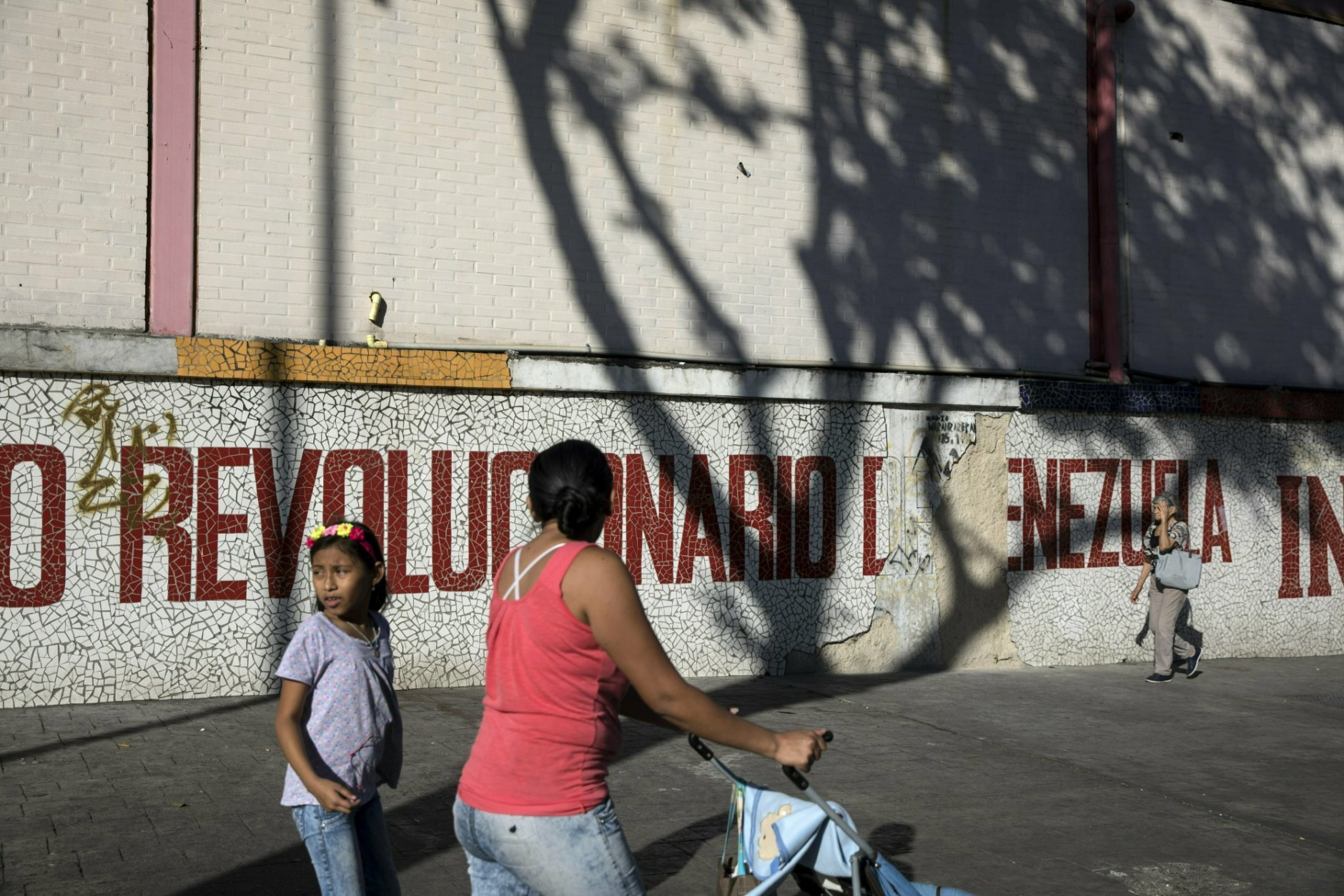 """People walk next to a mural that reads in Spanish """"Revolutionary of Venezuela"""" in Caracas, Venezuela, Friday, Jan. 25, 2019. Juan Guaido, the Venezuelan opposition leader who has declared himself interim president, appeared in public Friday for the first time in days and vowed to remain on the streets to usher in a transitional government, while President Nicolas Maduro dug in and accused his opponents of orchestrating a coup. (AP Photo/Rodrigo Abd)"""