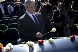 Austin Mayor Steve Adler lays a flower on top of the casket of WWII veteran Richard Overton at the Texas State Cemetery on Saturday, Jan. 12, 2019, in Austin, Texas.  Overton, who died on Dec. 27, 2018, was the nation's oldest living World War II veteran. (Nick Wagner/Austin American-Statesman via AP)