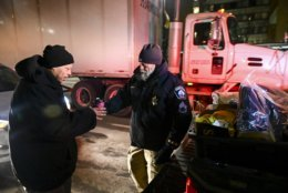 Minneapolis Police Sgt. Grant Snyder, right, hands a cup of hot chocolate to Dawone Boclair outside the public library on Hennepin Avenue in downtown Minneapolis, as the temperatures dipped well below freezing, Tuesday, Jan. 29, 2019. Snyder will be hitting the streets Tuesday and Wednesday night during the height of the big chill to check on the welfare of homeless people who haven't made it into a shelter. (Aaron Lavinsky/Star Tribune via AP)