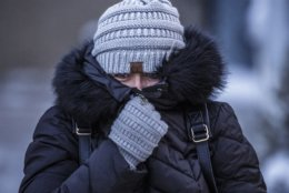 Andrea Billings keeps her face covered while walking across Center Street at its intersection with 1st Avenue in subzero temperatures on the way to her car after work Tuesday, Jan. 29, 2019, in downtown Rochester, Minn.  (Joe Ahlquist/The Rochester Post-Bulletin via AP)